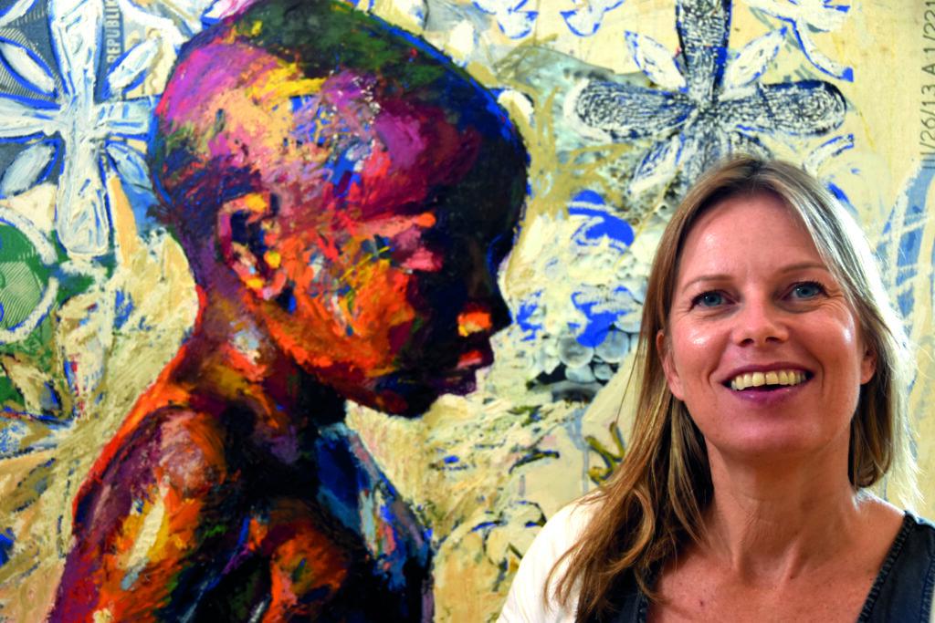 Foto van kunstenaar Bianca Berends met op de achtergrond een van haar schilderijen